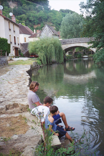 Julie, Patrick, and Christopher cool their feet in the River Yonne at Mailly le Chateau
